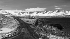 riding a patchwork road up North (lunaryuna) Tags: iceland northiceland northcoast northfjords solitude isolation silence damagedroad roadrepair solitaryroad spring season seasonalchange snowcappedmountains landscape coast seascape mountainrange lunaryuna blackwhite bwmonochrome