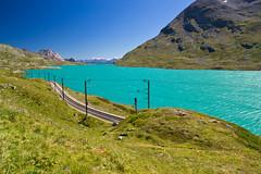 Lago Bianco below the Bernina pass, Switzerland (echumachenco) Tags: lake blue green mountain outdoor alps water grass rubble scree railway tracks sky lagobianco berninapass grisons graubnden switzerland schweiz suisse svizzera suiza nikond3100