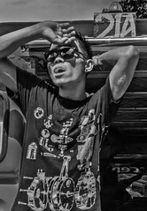 Jeepney 21A Passenger Agent (FotoGrazio) Tags: portrait youngman waynesgrazio pinoy streetphotography face shieldingfromthesun philippines documentaryphotography designertshirt tshirt jeepneysolicitor man streetportrait streetportraiture highcontrast gritty waynegrazio informalportrait filipino shout scar fotograzio blackandwhite lifeinthephilippines sunglasses