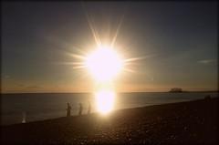 Chucking stones at sunset, Brighton (Wagsy Wheeler) Tags: brighton sussex westsussex beach brightonbeach westpier landmark sea seaside sun sunset evening dusk stones stone splash throwing