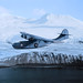A PBY-5A Catalina patrol bomber cruises against a backdrop of snow-clad mountains in Aleutian Islands, searching for enemy activity.