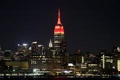 The Empire State Building is lit red in honor of the Fifth Annual Women's Health RUN 10 FEED 10. (apardavila) Tags: chryslerbuilding empirestatebuilding hoboken hudsonriver manhattan newyorkcity nyc skyline skyscraper