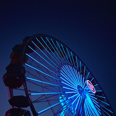ferris wheel at night. santa monica, ca. 2016. (eyetwist) Tags: eyetwistkevinballuff eyetwist night ferriswheel lines santamonica pier mamiya 6mf 50mm kodak portra 400 mamiya6mf mamiya50mmf4 kodakportra400 ishootfilm ishootkodak analog analogue film emulsion square 6x6 mediumformat 120 filmexif iconla recentlyprocessedfilm epsonv750 lenstagger losangeles la angeleno california santa monica pacificocean west coast socal los angeles symmetry santamonicapier light points summer amusement park architecture structure ferris wheel ride led blue pacificpark rides wharf spokes hub purple thrill heights geometric graphic
