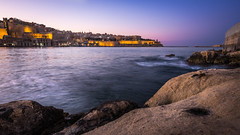 Valletta at sunset - Senglea, Malta - Seascape photography (Giuseppe Milo (www.pixael.com)) Tags: photo valletta senglea fujix sunset malta purple ultrawide rocks longexposure fuji14mm yellow xe2 fujifilm sea fujixe2 sun fuji14 magenta dusk travel motion photography fuji sky seascape orange europe geotagged landscape lisla mt onsale