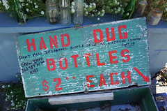 """Hand dug bottles"" (Eric Flexyourhead) Tags: porttownsend jeffersoncounty wa washington usa downtown waterstreet sign handmade weathered worn bottles handdugbottles contrast red green ricohgr"