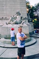 Like father, like son. (L. A. Nolan) Tags: 185mmf28 28mmequiv centralpark day fujifilmx70 manhattan men newyork newyorkcity newyorknewyork ny nyc outdoors outside people statue streetphotography thebigapple
