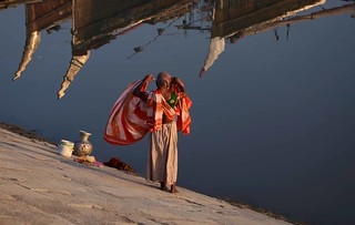 A woman taking open bath at bank of Kornofully river.