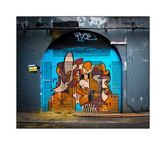 Graffiti (Decolife), South London, England. (Joseph O'Malley64) Tags: decolife graffiti streetart southlondon london england uk britain british greatbritain tunnel arch servicescabinet victorianstructure victorianrailwaytunnel brickwork render doors doubledoors lightingcables powersupply brackets anglebrackets sand laminateflooringplanks tonguegroove concrete granitekerbing tarmac doubleyellowlines cautionwetpaint mural muralist wallmural wall walls aerosol cans spray paint