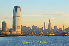Morning Magic Hour Colors & Tones of Goldman Sachs Tower with JC & NYC Skylines Plus Empire State Building (Photo #15b of LSP Series) from Liberty State Park Waterfront Walkway (Jersey City, NJ) (takegoro) Tags: york blue skyline sunrise buildings waterfront skyscrapers state manhattan midtown walkway park sachs new city jersey empire tower hudson building river harbor golden historic magic liberty site jersey hour goldman