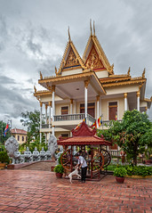 Wat Botum (Electricity Mule) Tags: street city summer sky people dog architecture clouds temple cambodia phnompenh wat watbotum