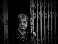 On Guard (gheckels) Tags: portrait woman home monochrome face lady fence gate chinatown bangkok candid guard streetphotography thai shutters shutter guarding