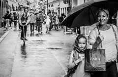 Happy in the rain (Morten Guttorm) Tags: street people bw salzburg rain umbrella shopping austria blackwhite europe candid mother zara