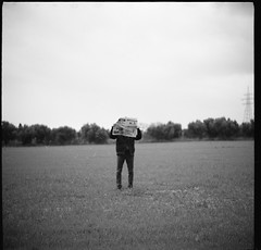 Wrong place to read the news (Salt.as) Tags: camera bw white 3 black 120 6x6 film field clouds analog lens outside person photography newspaper holding kodak tmax 5 portait foggy meadow figure fields medium format 100 28 90mm kiev vega developed 6c ilford minutes 2015 ilfosol 12b