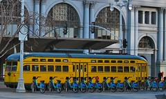 streetcar or bicycle? (idontkaren) Tags: sf sanfrancisco travel blue building yellow ferry ride market pavement transport bikes rental scene bicycles stop rack transportation embarcadero ferrybuilding rent streetcar juxtaposition arrangement fare decisions dilemma linedup flickrfriday