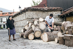 STREET - BULGARIA - Bankso - Old Lady Watches Log Maker (T R A V E L D O C U M E N T A R Y) Tags: street old blackandwhite woman color sofia chainsaw bulgaria logos carpenter spontaneous bansko plovdic