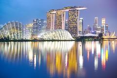 Singapore skyline at blue hour (Nicolas Lannuzel) Tags: nikonafsnikkor50mmf14g singapore buildings dusk asia marinabayfinancialcentre waterreflection water marinabaysands city darktable evening nikond600
