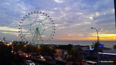 Wheel in sunset (MooMooAlien) Tags: ocean street trees sunset sky cloud sun beach car festival mall streetlamp philippines shoppingmall manila ferriswheel funfare smmallofasia