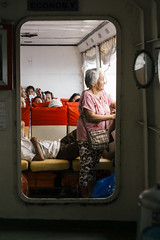 Elderly woman on the ferry to South Leyte, The Philippines (Merton Wilton) Tags: apsc asia availablelight boat brown carlzeissjena carlzeisspancolarmc1850 cebu countryside day documentary environmentalportraiture indoors island light m42mount mirrorless ocean people primelens red rural sea seascape ship social sonya6000 southeastasia streetphotography thephilippines travel visayanislands visayas water woman zeiss moody