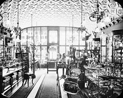 Shop Interior: silver, gold goods - indicative of wealth/trade. (National Library of Ireland on The Commons) Tags: thomasholmesmason thomasmayne thomashmasonsonslimited lanternslides nationallibraryofireland goldsmiths silversmiths jewellers display trays salvers chairs corridor carpet displaycases ceiling stuccowork locationidentified sharmandermottneill sharmandneill belfast shop jeweller ornaments silver platter reflection clocks ornamentalceiling