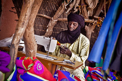 Tailor in the market of Gorom Gorom, Burkina Faso (NeSlaB .) Tags: poverty africa travel colors look canon photo village veil dress market traditional country young culture photojournalism tribal clothes ornaments tradition tribe ethnic tailor dressmaker developingcountries burkinafaso reportage nationalgeographic afrique goromgorom ethnography ethnology ethnies neslab davidecomelli