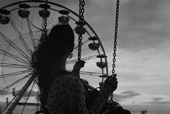 Carnival Date (AnniversaryRoad) Tags: 35mm 50mm bw canada ft2 fair kodak manitoba nikkormat nikon nipponkogaku redriverex redriverexhitibition tmax theex winnipeg analog black blackandwhite carnival chains clouds countyfair date ferris ferriswheel festival film hair monochrome night outside sky swing white wind woman young outdoor