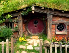Burgundy Hobbit-hole (Rebekah H. Photographie) Tags: wood red newzealand summer vacation green nature grass rock stone mailbox fence garden outside wooden bush rocks stones hill fences postbox grasses hobbit bushes thehobbit hobbiton