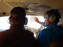 """Guide Sean giving Jim, our bush pilot, an assist with blocking the sun -- note the """"sun blocker"""" is a flimsy little piece of paper that was pretty much see-thru.  Those Alaska bush pilots surely know how to improvise...!"""