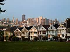 San Fran Painted Ladies (creditflats) Tags: sanfrancisco california park city houses ladies light sunset usa west color colour skyline architecture pen coast colorful painted shingles victorian olympus porch handheld colourful transamerica scape iconic alamosquare ep1 steiner ois