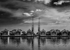 Toy village revisited (aistora) Tags: uk houses light shadow england sky blackandwhite bw white black color colour reflection london water monochrome thames skyline architecture clouds composition contrast zeiss buildings reflections river skyscape t mono mirror waterfront conversion britain sony symmetry cranes filter docklands ripples 24mm residential development excel royalvictoriadock topaz irfan sensitivity irfanview sonnar convert nex canningtown mirrorless maistora 5r sel24f18za nex5r