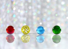Marble Row (nikagnew) Tags: blue red colour reflection green yellow four bright bokeh marbles colourful