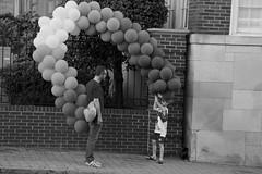 """Son, how are we going to get them all into the car?"" (tvdflickr) Tags: balloons boy man collection group atlanta atlantageorgia street monochrome nikon d750"