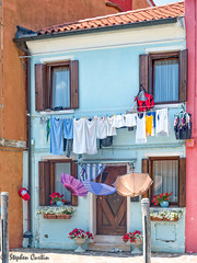 Hung out to Dry (stephencurtin) Tags: umbrella pail flowers laundry drying blue red wood doors shutters burano italy tourist everyday
