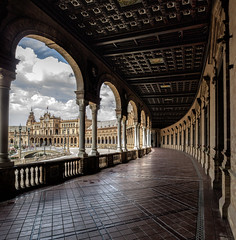 The corridors of power (grbush) Tags: travel architecture clouds sevilla spain corridor arches seville panasonic tiles g3 espania m43 lumixg plazadeespania olympusm918mm