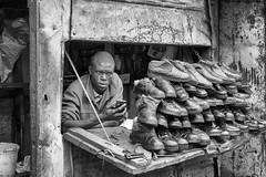 Selling shoes. Black shoes (Bernard_Menett) Tags: kenya kibera nairobi shoe shop slum street bw