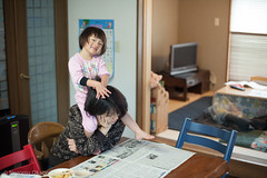 newspaper (Nozomu Okabe) Tags: family home girl newspaper kid child daughter mother mischievous piggyback sumire