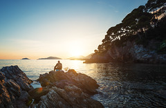 Sunset Fishing (Philipp Klinger Photography) Tags: old travel italien blue trees light sunset sea vacation sky italy orange cliff holiday fish seascape man tree nature water yellow rock pine landscape island evening fishing rocks warm mediterranean italia angle liguria hill wide warmth oldman cliffs pines fisher portovenere mediterraneansea lerici tellaro ligurien fiascherino