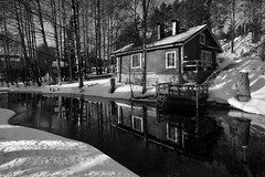 Streamside Cottage (Miguel Virkkunen Carvalho) Tags: morning travel trees windows winter light shadow blackandwhite bw sun sunlight house snow cold reflection ice nature water composition digital forest canon suomi finland river photography pier wooden woods stream europe frost mood doors riverside natural outdoor branches north cottage freezing sigma atmosphere scene scenario nordic birch trunks february accommodation scandinavia northern ambience photooftheday picoftheday margin 2015 porras sigma1020 streamside bestoftheday canoneos1000d portaannahkurinverstas