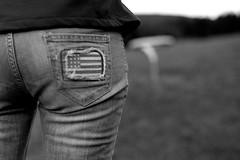 A Flag (Leica M6) (stefankamert) Tags: stefankamert flag street girl woman bw sw baw blackandwhite blackwhite dof grain leica m6 m leicam6 rangefinder mirrorless voigtlnder nokton ilford fp4 film analog bokeh trousers pants jeans