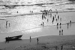 Fishermen on the beach (yuriye) Tags: sea people india black reflection beach water grey evening boat fishing fisherman shine fishermen ngc wave down kerala varkala yuriye