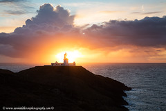 Sunset at Strumble Head Lighthouse (Ian Middleton: Photography) Tags: ocean uk travel light sunset sea vacation lighthouse holiday tourism wales clouds coast unitedkingdom britain rocky beam coastal british welsh lit beacon strumblehead pembrokeshire headland fishguard