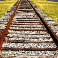 Tired Tracks (fillzees) Tags: rr railroad tracks rails abandoned old spur railway rusty iron steel ties ballast perspective vanishingpoint siding symmetry symmetrical crosstie rail rusted wood grass