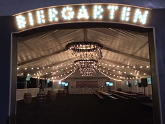 BIERGARTEN tent sign and indoor custom 8 ft wreath chandeliers with festoon lighting provided by Intelligent Lighting Design - Austin, Texas. Location: Circuit of the Americas (US Grand Prix Formula One)