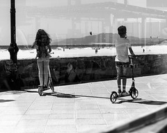 En linea (Franci Esteban) Tags: streetphotography fotografacallejera sombra sombras nios patinete blancoynegro blackandwhite paseo tarifa