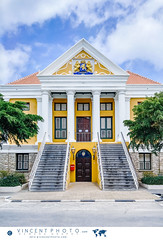 The Town Hall dates from 1860. The symmetrical building houses the Parliament of the Netherlands Antilles on its eastern side, and the Court of Justice on its western side. (Vincent Demers - vincentphoto.com) Tags: abcislands amriquedusud antilles antillesnerlandaises architecture carabes caribbean caribbeanisland curacao curaao destinationdevoyage destinationtouristique dutchcaribbean dutchcaribbeanisland facade faade historic historique iledescarabes kingdomofthenetherlands netherlandsantilles parlement parliament photodevoyage photographiedevoyage punda royaumedespaysbas sitedupatrimoinemondialdelunesco southamerica symmetry tourism tourisme townhall travel traveldestination travellocation travelphoto travelphotography trip unescoworldheritagesite unesco voyage wilhelminapark wilhelminaplaza wilhelminasquare wilhelminaplein willemstad siteunesco cw
