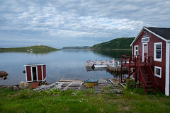 Red Bay - Labrador (Dolores Harvey) Tags: outhouse labrador ocean stillwater stillness doloresharvey red redhouse redbay redbaylabrador canvassingtheneighbourhood canvassingtheneighbourhoodphotography canvassingtheneighbourhoodcom grass clouds nature dory row boat stage wharf waterfront calm
