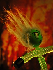 Hair-raising backlight (flowergirlaaa) Tags: colour red green fire fluorescent hair standingonend backlight macro halloween scared scary toy macromonday backlit hmm