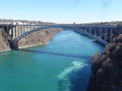 Niagara Falls. The famous Rainbow Bridge below the falls which links the Canadian and American cities of Niagara Falls. (denisbin) Tags: bridge river niagarafalls boat border rainbowbridge maidinthemist usacanadaborder