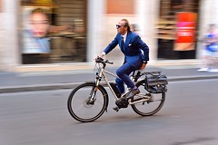 Suited and booted (jeremyhughes) Tags: pocketsquare italy rome viadelcorso street cyclist suit suited smart stylish bluesuit cycling commuter commuting urban city bicycle bike movement motion speed panning nikon d750 sigma 50mm 50mmf14 brogues socks electricbike