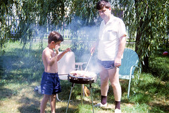 Dad cooks up some smokey barbecue ribs and chicken while a skinny young me waves the smoke away. He never used barbecue sauce, but smothered everything in delicious spices. In the corner of our back yard. Milford Connecticut. August 1966. (wavz13) Tags: summer kodachrome oldphotographs weepingwillow oldphotos oldfamilyphotos oldslides oldfamilyslides vintagephotos weepingwillows oldphotography oldchairs vintagephotographs vintagekids familyslides oldsnapshots antiquechairs vintagechairs vintagephotography vintageteens vintageteenagers vintageslides vintagefamilyphotos vintagesnapshots connecticutphotography oldnewengland 1960sphotos teenagememories connecticutphotos vintagelawnchairs 1960sphotography oldlawnchairs vintageconnecticut vintagelawnfurniture vintagekodachrome vintagenewengland oldconnecticut oldmilford oldlawnfurniture teenmemories 1960sphotographs oldkodachrome connecticutphotographs oldconnecticutphotography oldconnecticutphotos vintagewoodmont oldwoodmont vintagemilford antiquelawnchairs vintagefamilyphotography antiquelawnfurniture 1960smilford oldfamilyphotography 1960swoodmont vintagenewenglandphotos oldnewenglandphotos vintagenewenglandphotography oldnewenglandphotography 1960snewengland
