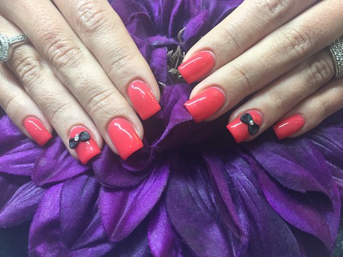 Acrylic nails with red gel polish and 3D acrylic bow